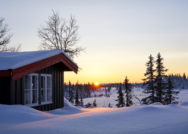 Hytte i solnedgang.